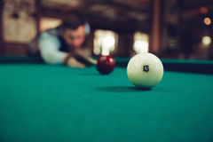 Man playing billiard. Young man concentrating while playing billiard Royalty Free Stock Photos