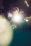 Man playing billiard. Young man concentrating while playing billiard with light spots Stock Photo