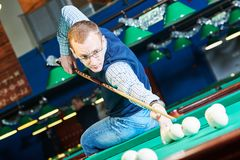 Man playing billiards in club. Billiards game. Russian pyramid. man playing billiard in club Royalty Free Stock Photography