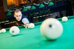 Man playing billiards in club. Billiards game. Russian pyramid. man playing billiard in club. Focus on ball Royalty Free Stock Photography