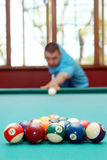Man playing billiards focus on balls Royalty Free Stock Photography