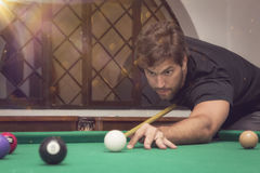 Man playing billiards in a pool table. Stock Image
