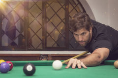 Man playing billiards in a pool table. Royalty Free Stock Photo
