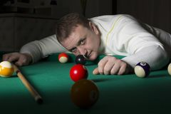 Playing billiards. The man is playing billiards. Score the ball into the pocket. Gambler Royalty Free Stock Photography