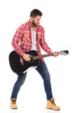 Man playing the black acoustic guitar Stock Photos