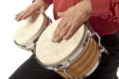 Man playing bongo set on his lap Royalty Free Stock Image