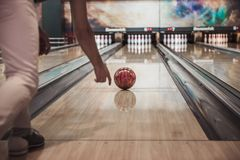 Man playing bowling. Cropped image of a man throwing a red bowling ball Royalty Free Stock Photography