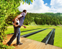 Man playing bowling. With football ball on the lawn Royalty Free Stock Photos