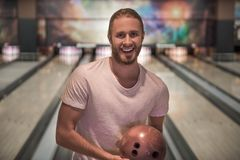 Man playing bowling. Handsome young man is holding a bowling ball, looking at camera and smiling ready to play bowling Royalty Free Stock Photography