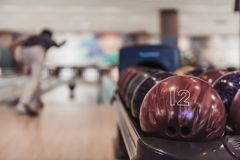 Man playing bowling. Man throwing a red bowling ball, colorful balls in the foreground Stock Image