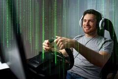 Man playing car racing video game at home. Technology, gaming, entertainment and people concept - happy smiling young man in headphones with pc computer playing royalty free stock images