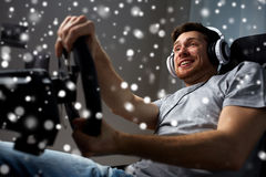 Man playing car racing video game at home. Technology, gaming, entertainment and people concept - happy smiling young man in headphones with pc computer playing royalty free stock image
