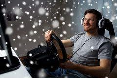 Man playing car racing video game at home. Technology, gaming, entertainment and people concept - happy smiling young man in headphones with pc computer playing stock photography