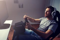 Man playing car racing video game at home. Technology, gaming, entertainment and people concept - young man in headphones with pc computer playing car racing stock photography