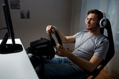 Man playing car racing video game at home Stock Photos