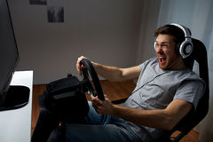 Man playing car racing video game at home. Technology, gaming, entertainment and people concept - young man in headphones with pc computer playing car racing royalty free stock image