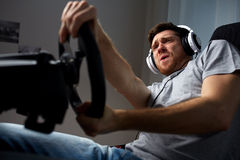 Man playing car racing video game at home. Technology, gaming, entertainment and people concept - young man in headphones with pc computer playing car racing stock photos