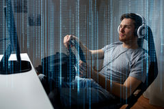 Man playing car racing video game at home. Technology, gaming, entertainment and people concept - young man in headphones with pc computer playing car racing royalty free stock photos