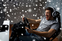 Man playing car racing video game at home. Technology, gaming, entertainment and people concept - young man in headphones with pc computer playing car racing stock photo