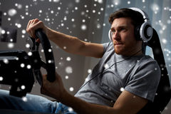 Man playing car racing video game at home. Technology, gaming, entertainment and people concept - young man in headphones with pc computer playing car racing royalty free stock images