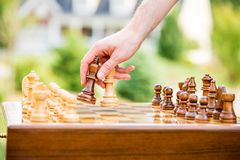 Man playing chess on board outdoors. Strategy and competition concept royalty free stock image