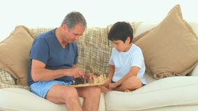 A man playing chess with his grandson. On the sofa stock video footage