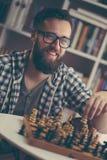 Man playing chess. At home, enjoying his leisure time Royalty Free Stock Photos