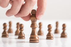 Man playing chess moving black king piece in a close up view Royalty Free Stock Photo