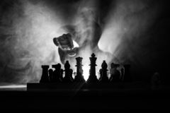 Man playing chess. Scary blurred silhouette of a person at the chessboard with chess figures. Dark toned foggy background. Selective focus. Horror concept stock images