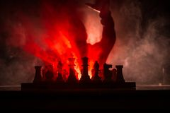 Man playing chess. Scary blurred silhouette of a person at the chessboard with chess figures. Dark toned foggy background. Selective focus. Horror concept stock photo