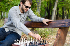 Man playing chess on a wooden bench Stock Image