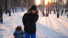 Man playing with children, rolling them on snowtube.snow winter landscape. outdoors sports stock video footage