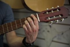 Man playing a classic guitar. Hand picks up the strings on the guitar. stock photo