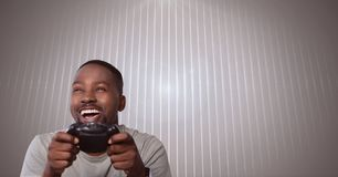 Man playing with computer game controller with bright ridged background Royalty Free Stock Images