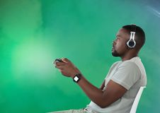 Man playing with computer game controller with green fog background. Digital composite of man playing with computer game controller with green fog background Royalty Free Stock Photography
