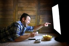 Man playing on a console on the joystick before the big TV Royalty Free Stock Images