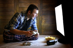 Man playing on a console on the joystick before the big TV Royalty Free Stock Photos