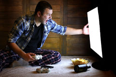Man playing on a console on the joystick before the big TV Stock Photos