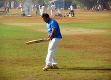 Man playing cricket on the grass of the stadium in Mumbai India Royalty Free Stock Photography