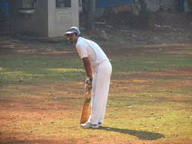 Man playing cricket on the grass of the stadium in Mumbai India Stock Photo