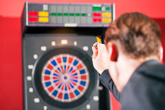 Man playing darts. Aiming with the dart to hit the target, Focus only on dart Stock Photos