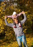 Man playing with daughter at autumn park Royalty Free Stock Photo