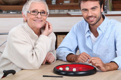 Man playing dice with older woman Stock Image