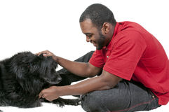 Man Playing with Dog. Black African American man playing with a dog stock photo