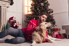 Man playing with dog at christmastime. Bearded young men man playing with golden retriever dog at christmastime royalty free stock photos