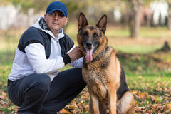Man Playing With Dog German Shepherd In Park. Man Sitting Outdoors With His Pet Dog German Shepherd stock image