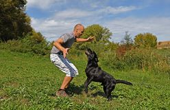Man is playing with dog Royalty Free Stock Photography