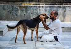 A man playing with dog at temple in Gaya, India.  Royalty Free Stock Images