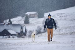 Man playing with dog in winter landscape royalty free stock photo