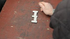 Man Playing Dominoes On The Rough Table Top stock footage